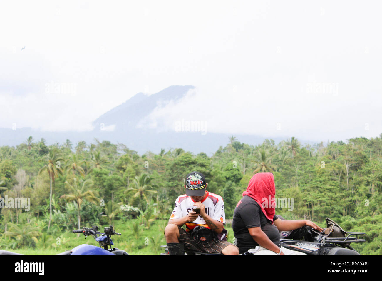 Two tour guides take a break from our quadbike tour. Ubud, Bali, Indonesia. - Stock Image