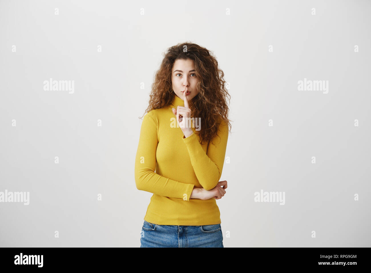Close up portrait of cute lovely attractive uncertain unsure with entrepreneur making hush gesture isolated on gray background copy-space - Stock Image