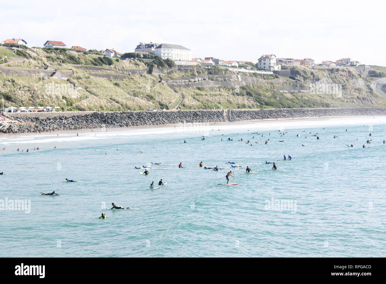 A surfing and beach loving town of Biarittz. Surfers fill the water. - Stock Image