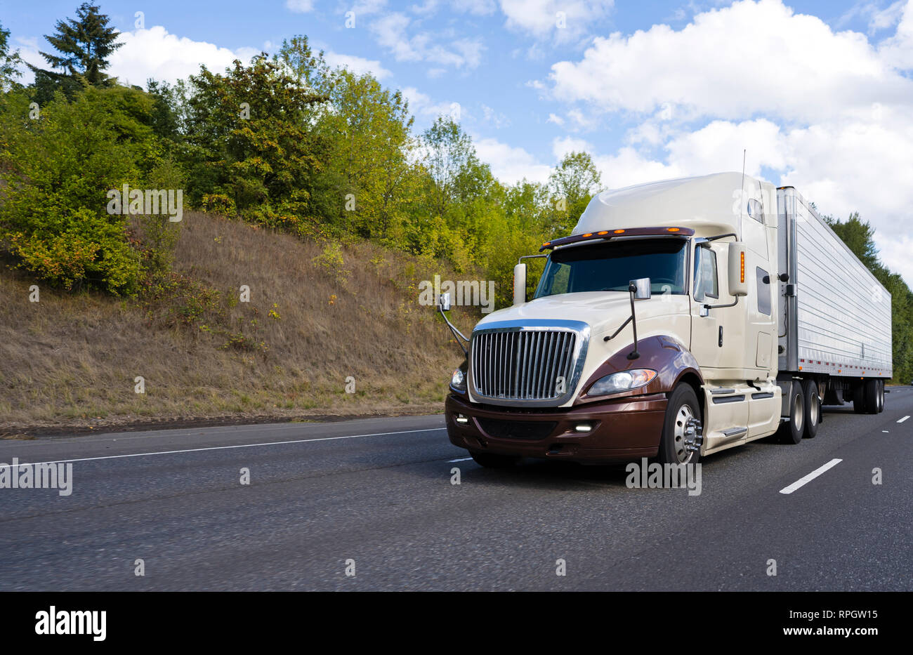 Two tones big rig American modern bonnet long haul semi truck with cabin with compartment for driver rest transporting cargo in refrigerated semi trai - Stock Image