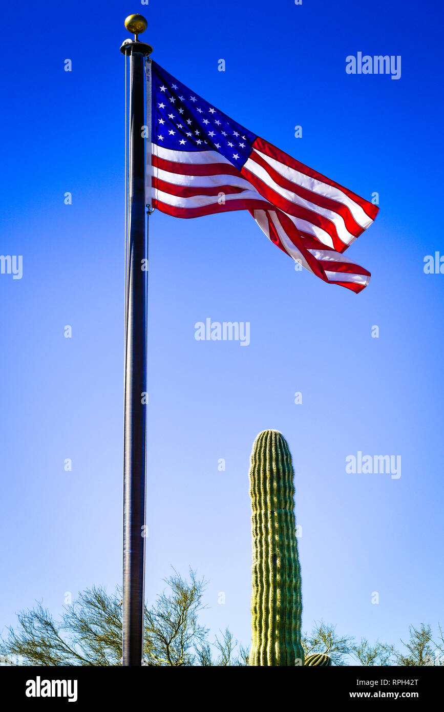 A tall flag pole with an American Flag waving in the wind ...