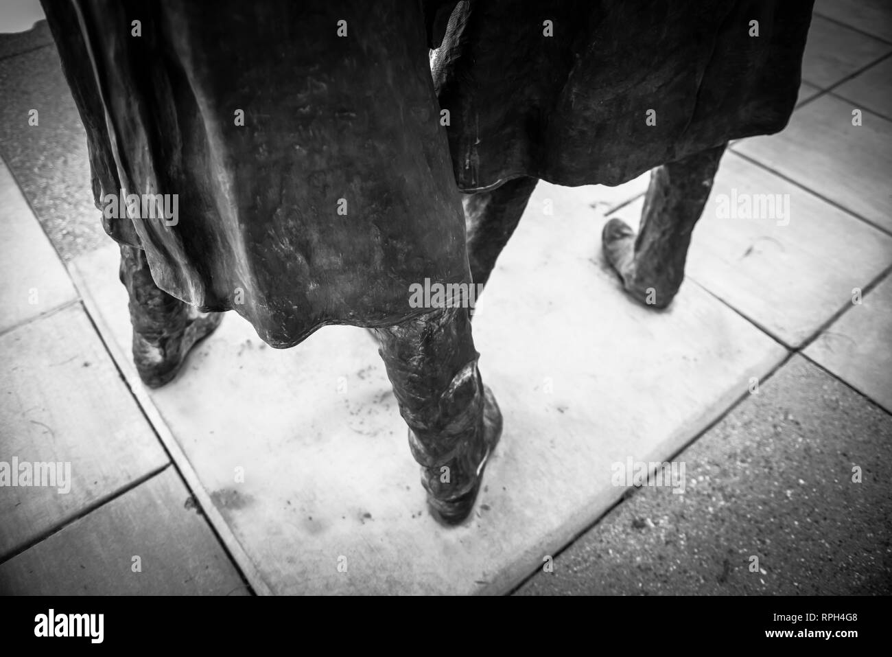 A dramatic black & white view of The lower half of two bronze statues of Doc Holiday and Wyatt Earp wearing their cowboy duster coats at the Southern  - Stock Image