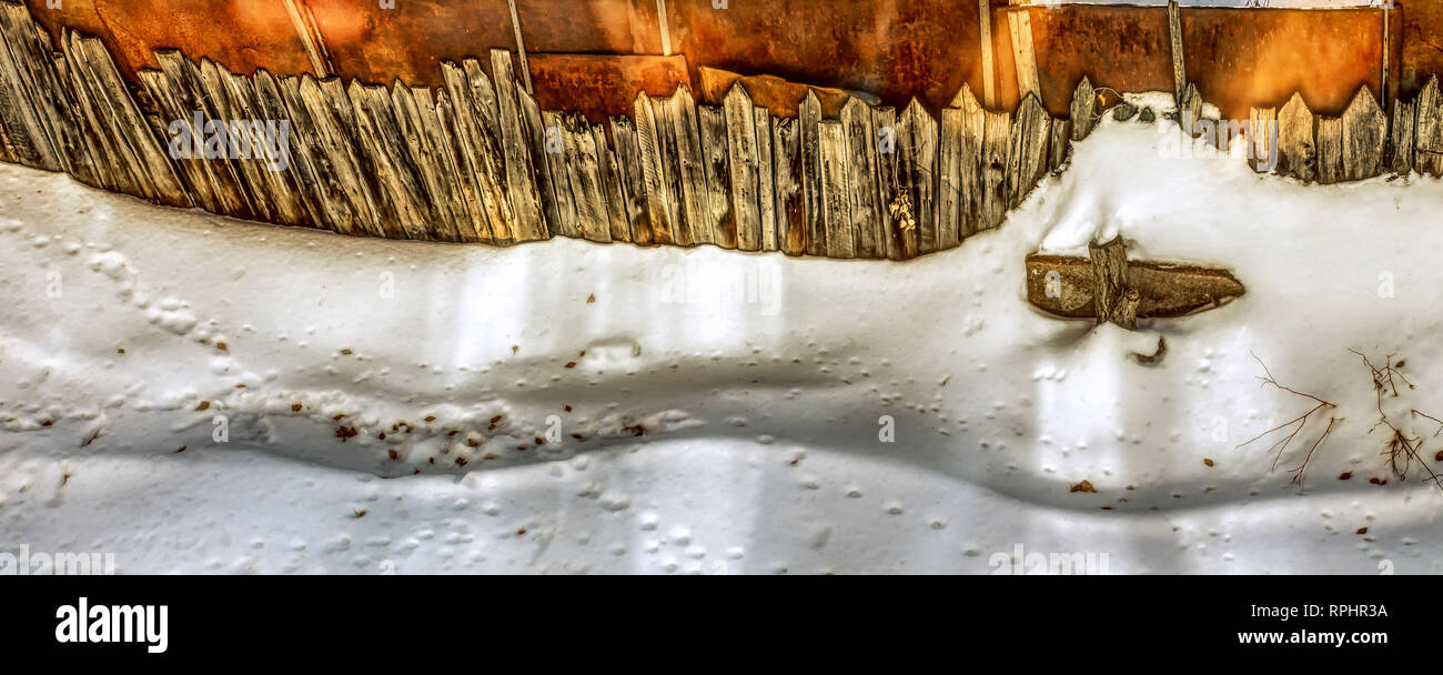 Minimalist shot of huge snowdrift under the wooden rustic fence. - Stock Image