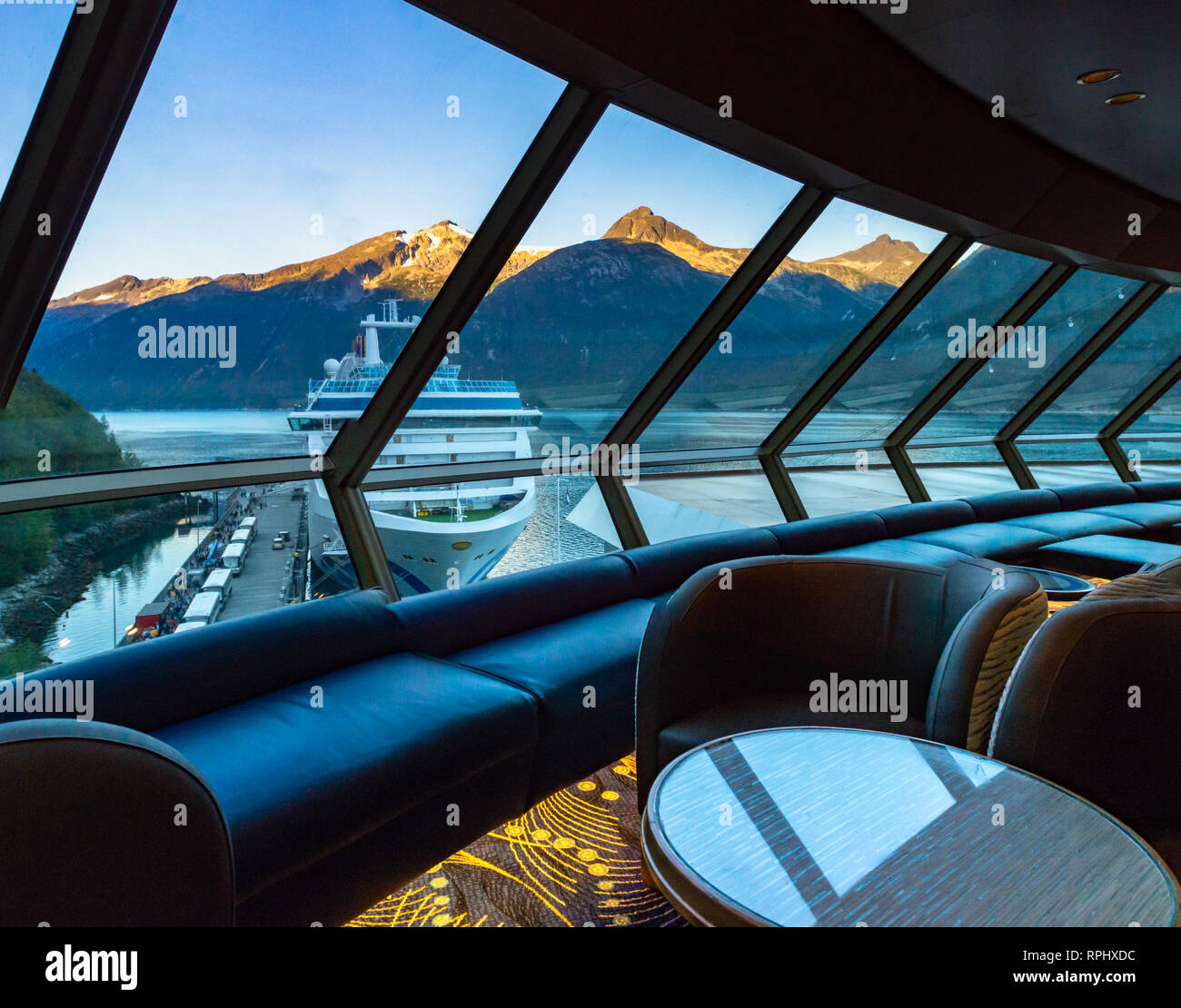 September 15, 2018 - Skagway, AK:  Sunrise on mountains and Princess Cruises ship berthed in port, early morning  from inside a quiet Crow's Nest Loun - Stock Image