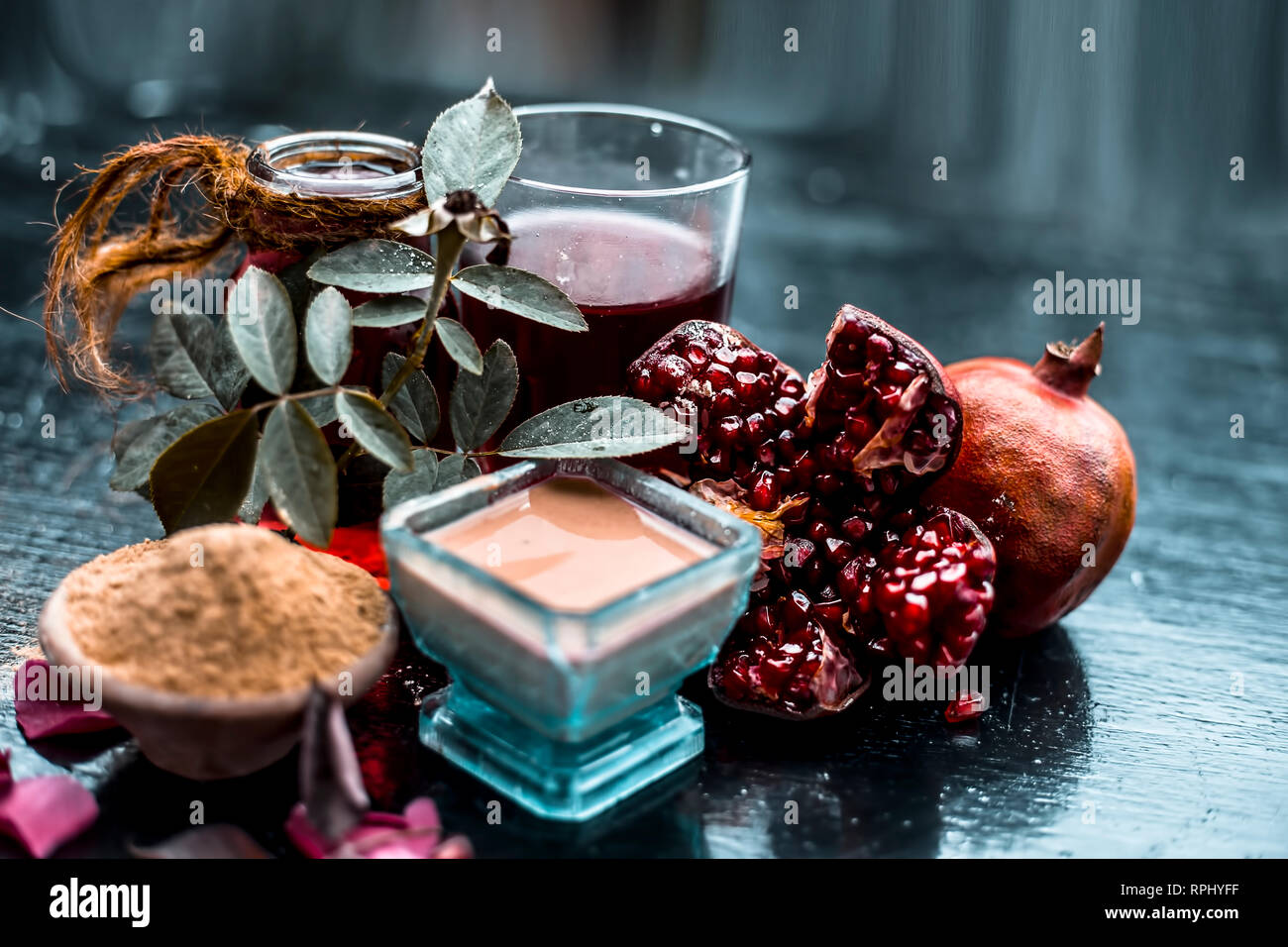 Herbal and organic face pack of pomegrante with some raw pomegranate juice and fuller's earth or mulpani mitti,and rose water on wooden surface - Stock Image