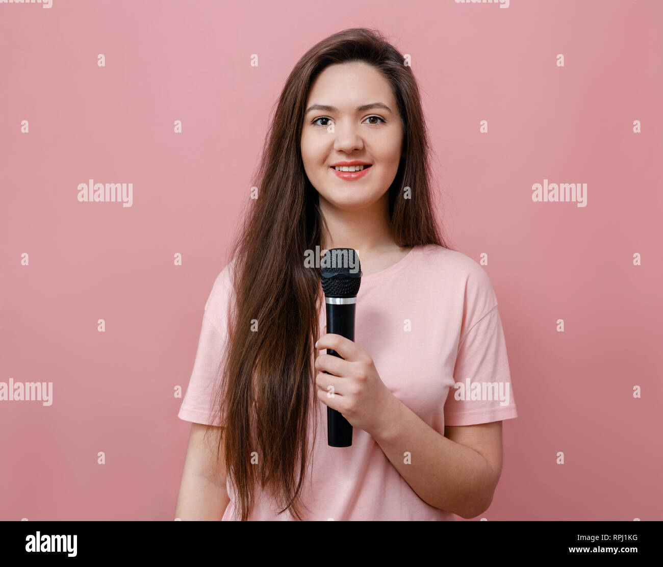 young woman with microphone in hand  on pink background - Stock Image