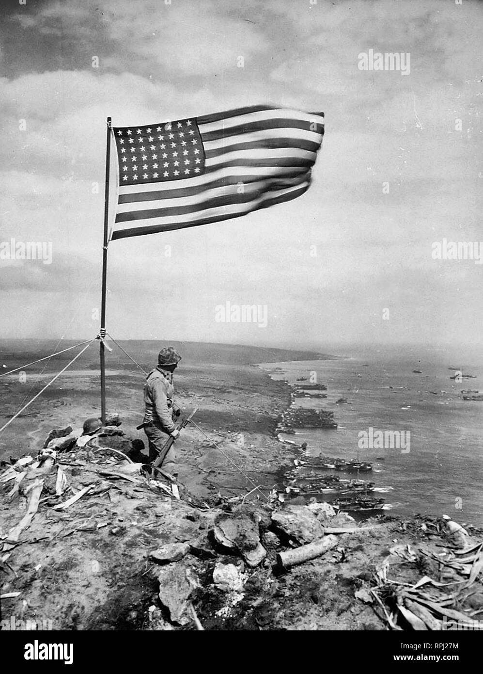 From the crest of Mount Suribachi, the Stars and Stripes wave in triumph over Iwo Jima after U.S. Marines had fought their way inch by inch up its steep lava-encrusted slopes - Stock Image