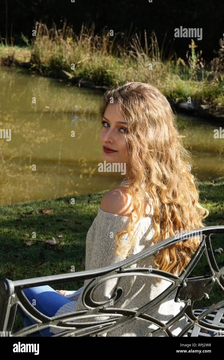 Young woman or girl with long flowing hair looking back over her bare shoulder sitting on a bench with rural country background - Stock Image
