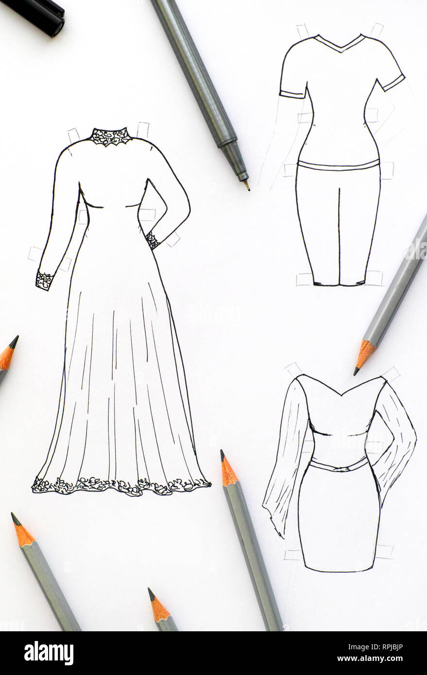 Hand drawing clothes for paper doll with black pen and pencils. - Stock Image