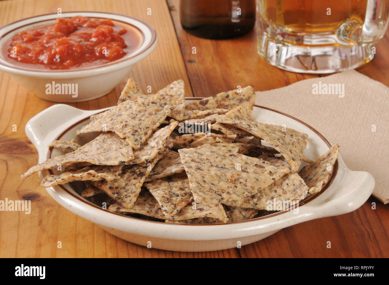 A Bowl Of Rice And Bean Tortilla Chips With Salsa And Beer Stock
