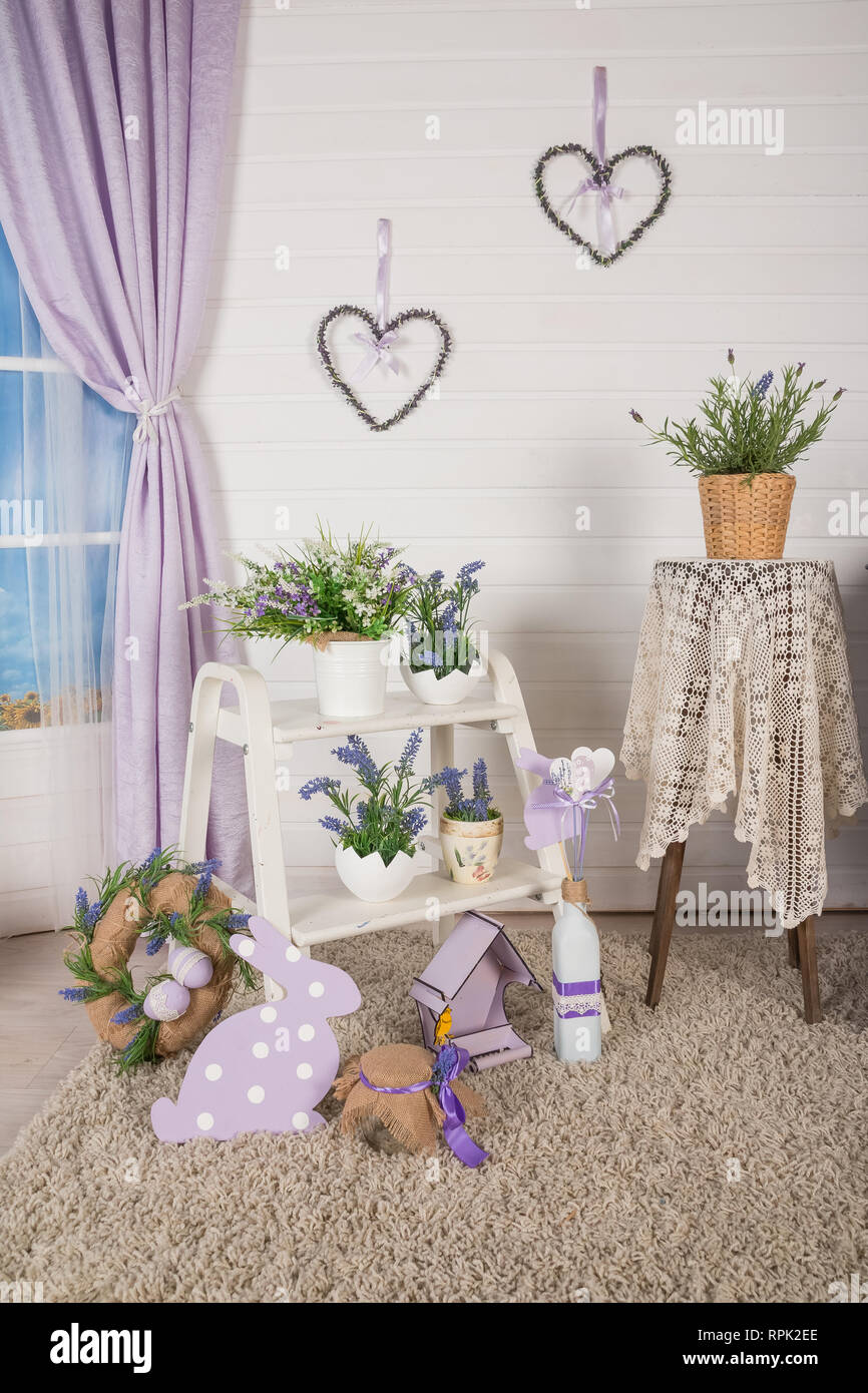 Shabby chic interior decor for farmhouse. Lavende,plant and vintage table,shelf over pastel wall. Provence home decoration.Garden chair with flowers - Stock Image