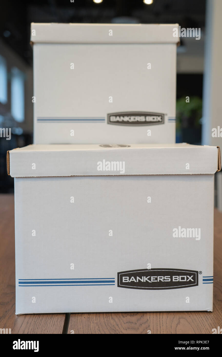August 9 2018 - Calgary, alberta - Canada - Bankers box to arrange files on office wood table - Stock Image