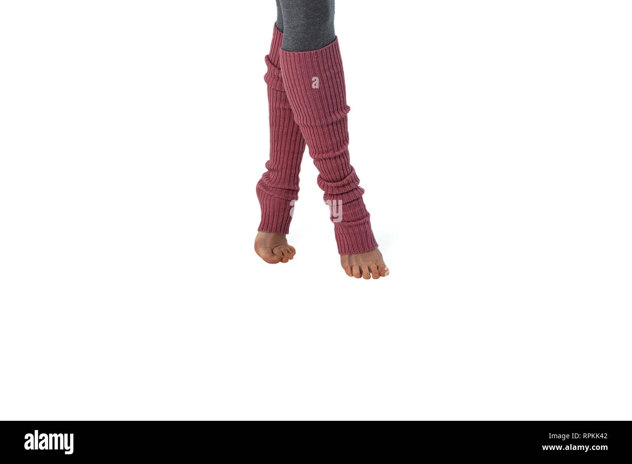 a9faff24292e8 young girl in pink leggings, engaged in pilates standing on fingers. White  background. isolate