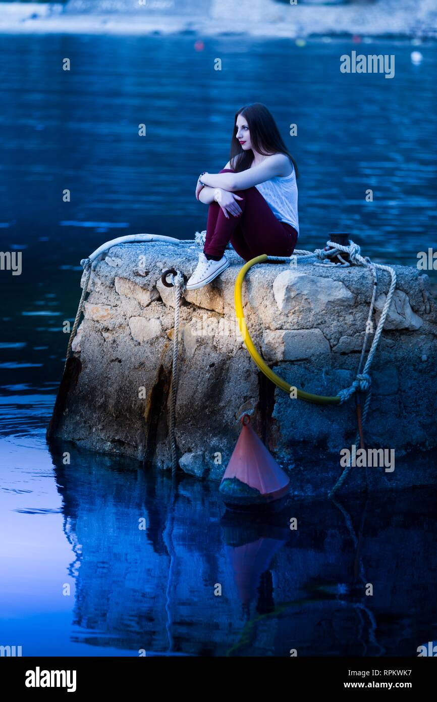 18-20 years teen girl is sitting on big quay alone looking in distance serious - Stock Image