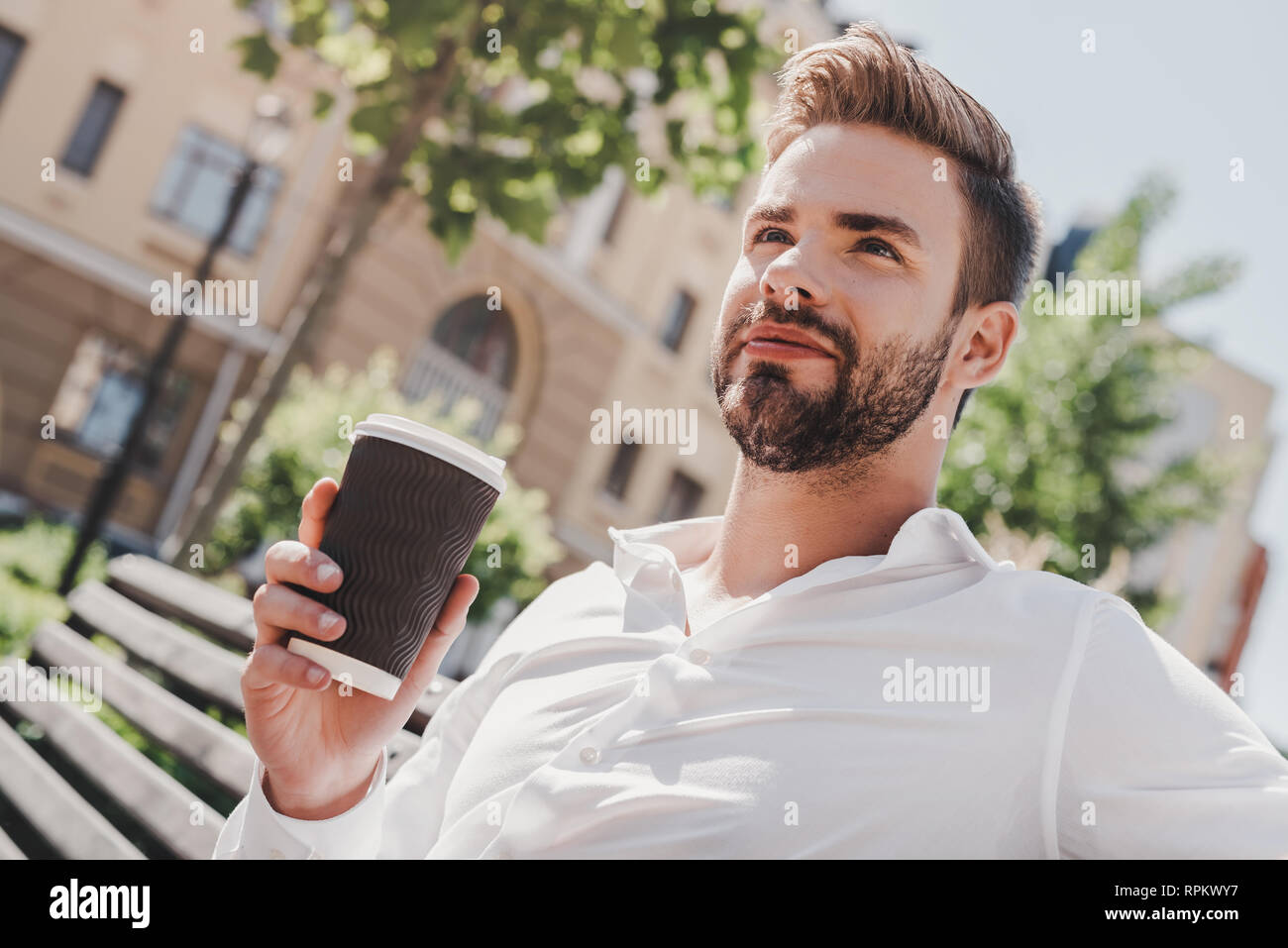 Close up of handsome young man sitting on a bench in the park and holding cup of coffee. Man dressed in a white shirt, looking away. Summertime, relax - Stock Image