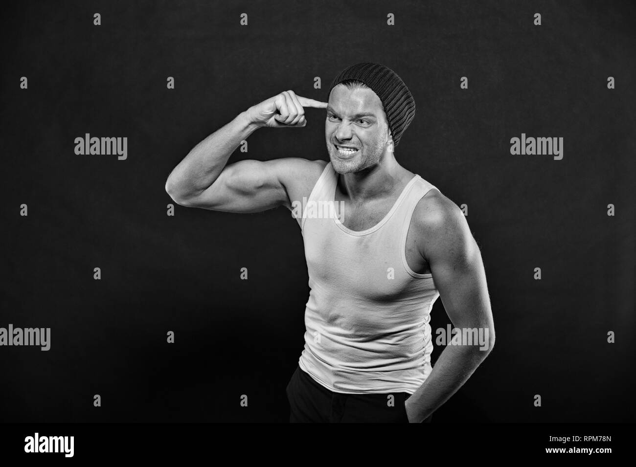 Macho with angry face. Man with finger at head. Athlete in fashion vest and hat with hand gesture. Anger and stress. Power in fitness and sport, black and white. - Stock Image
