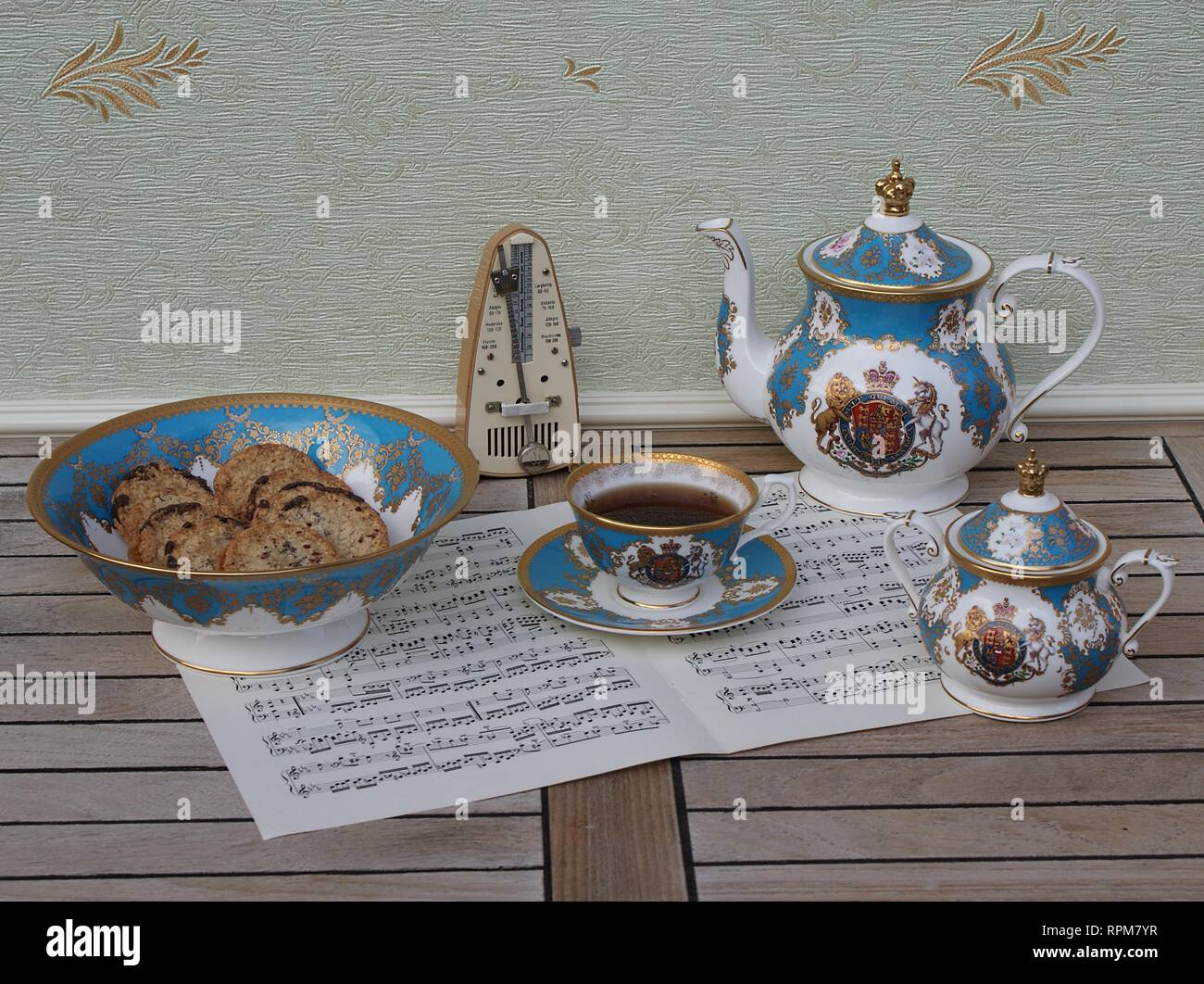 English teacup with saucer, teapot, sugar bowl and a cake bowl with cookies, fine bone china porcelain, and a metronome for music on a sheet of music - Stock Image