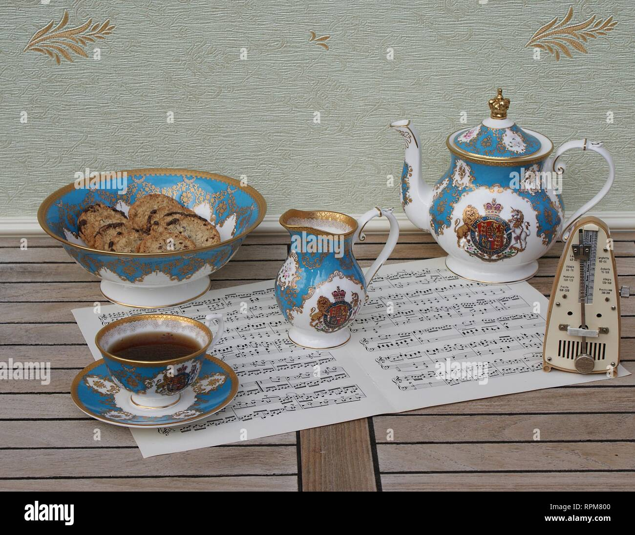 English teacup with saucer, teapot, cream jug and a cake bowl with cookies, fine bone china porcelain, and a metronome for music on a sheet of music - Stock Image