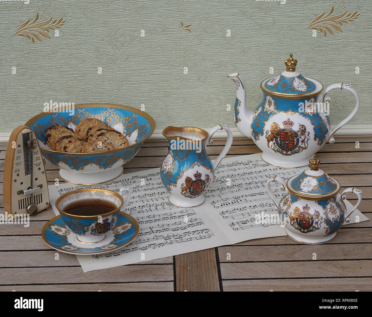 English teacup with saucer, teapot, sugar bowl, cream jug and a cake bowl with cookies and a metronome for music on a sheet of music - Stock Image