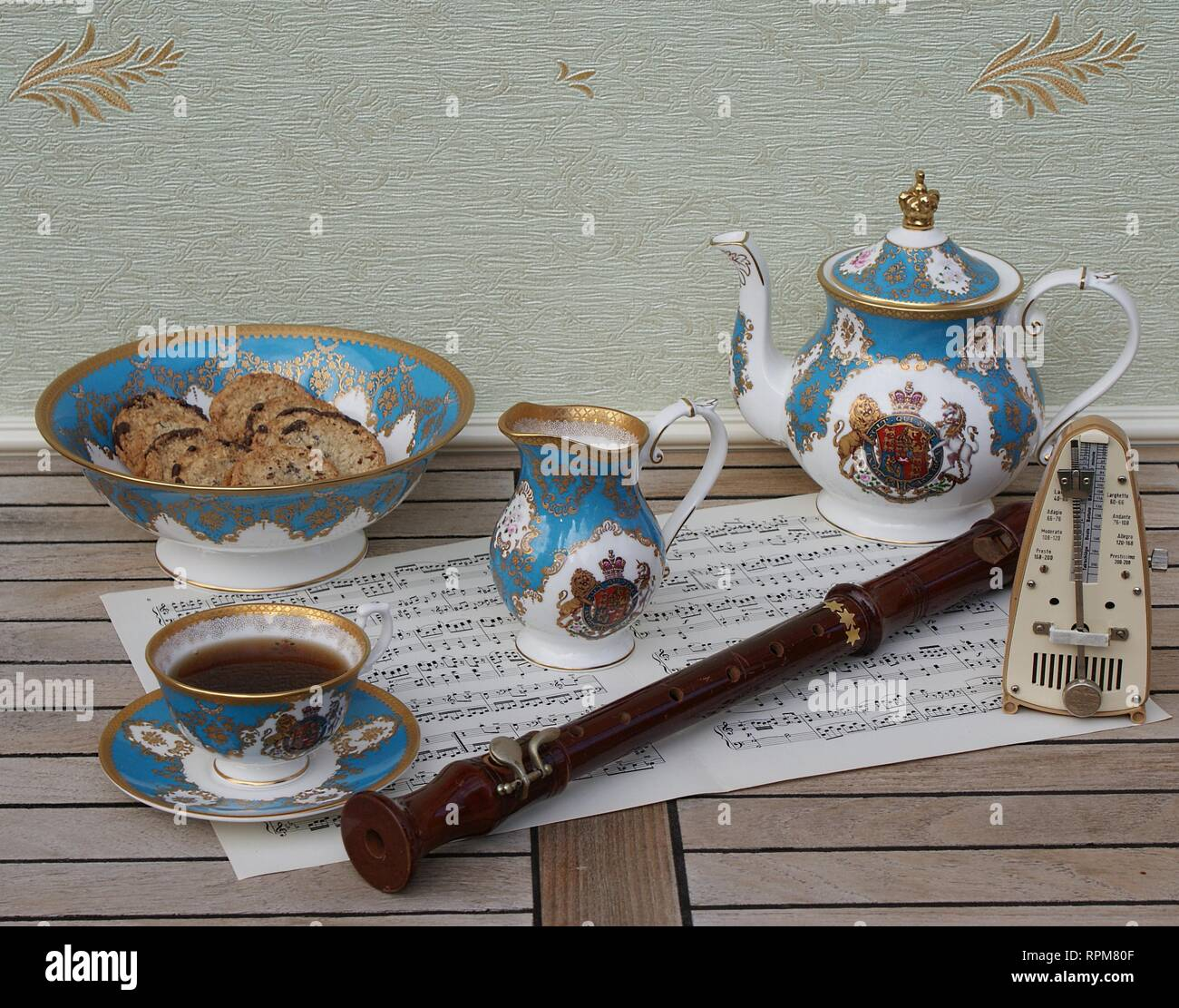 English teacup with saucer, teapot, cream jug and a cake bowl with cookies, a metronome for music and a block flute on a sheet of music - Stock Image