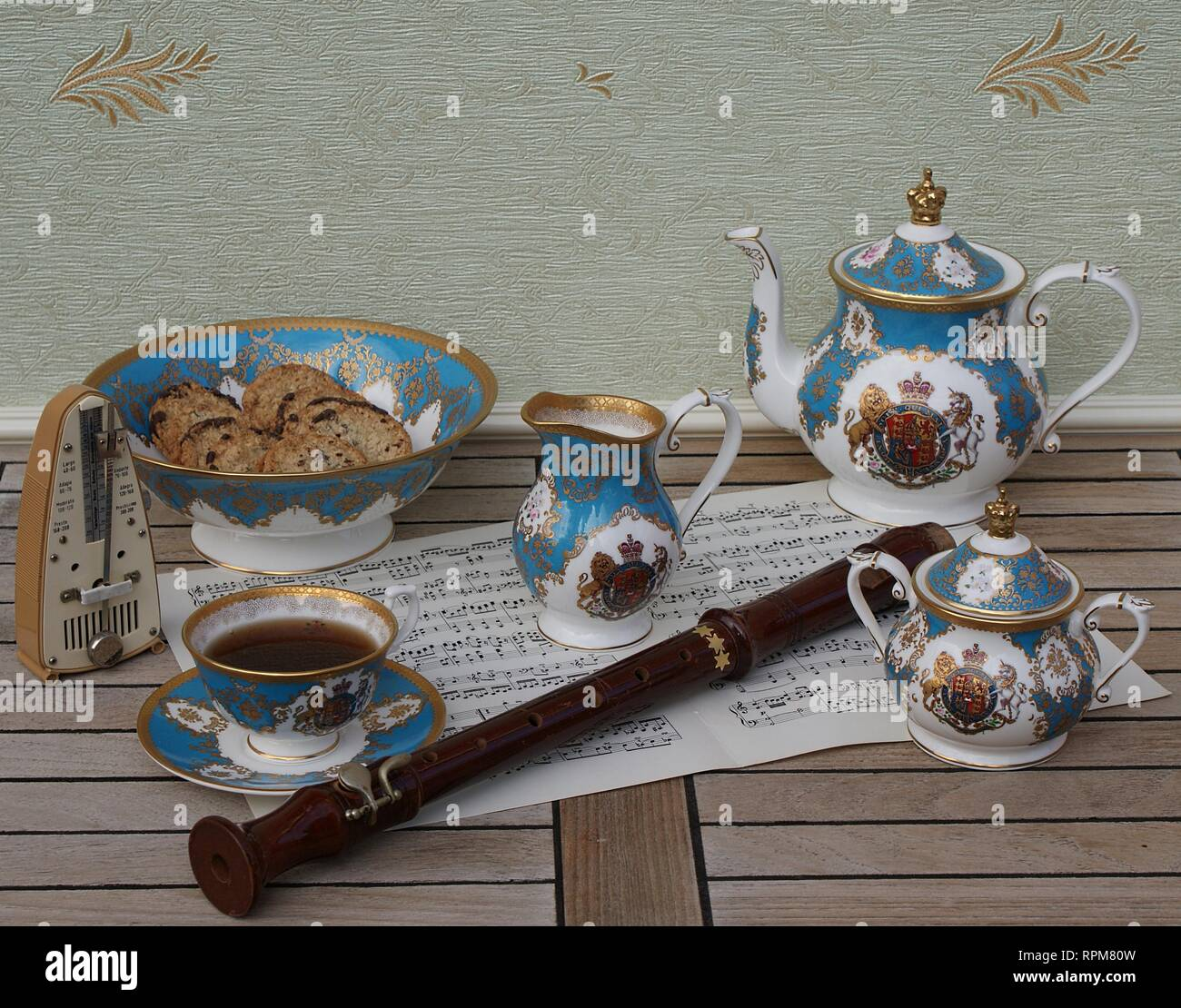 English teacup with saucer, teapot, sugar bowl, cream jug and a cake bowl with cookies, metronome for music and a block flute on a sheet of music - Stock Image
