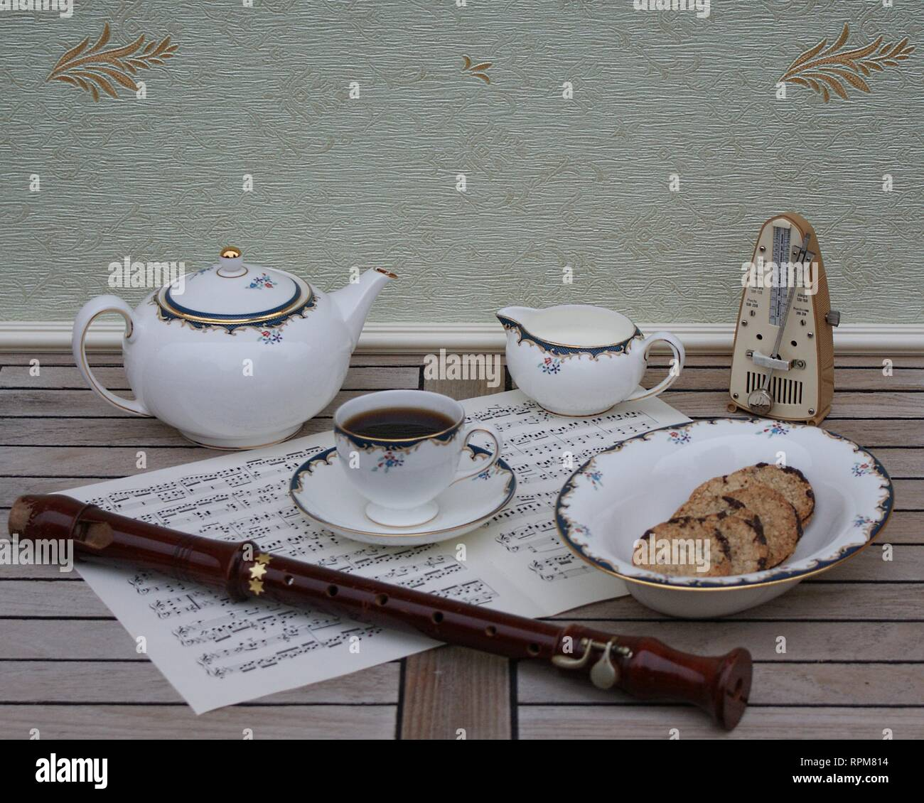 English teacup with saucer, teapot, cream jug and a cake bowl, fine bone china porcelain, metronome for music and a block flute on a sheet of music - Stock Image