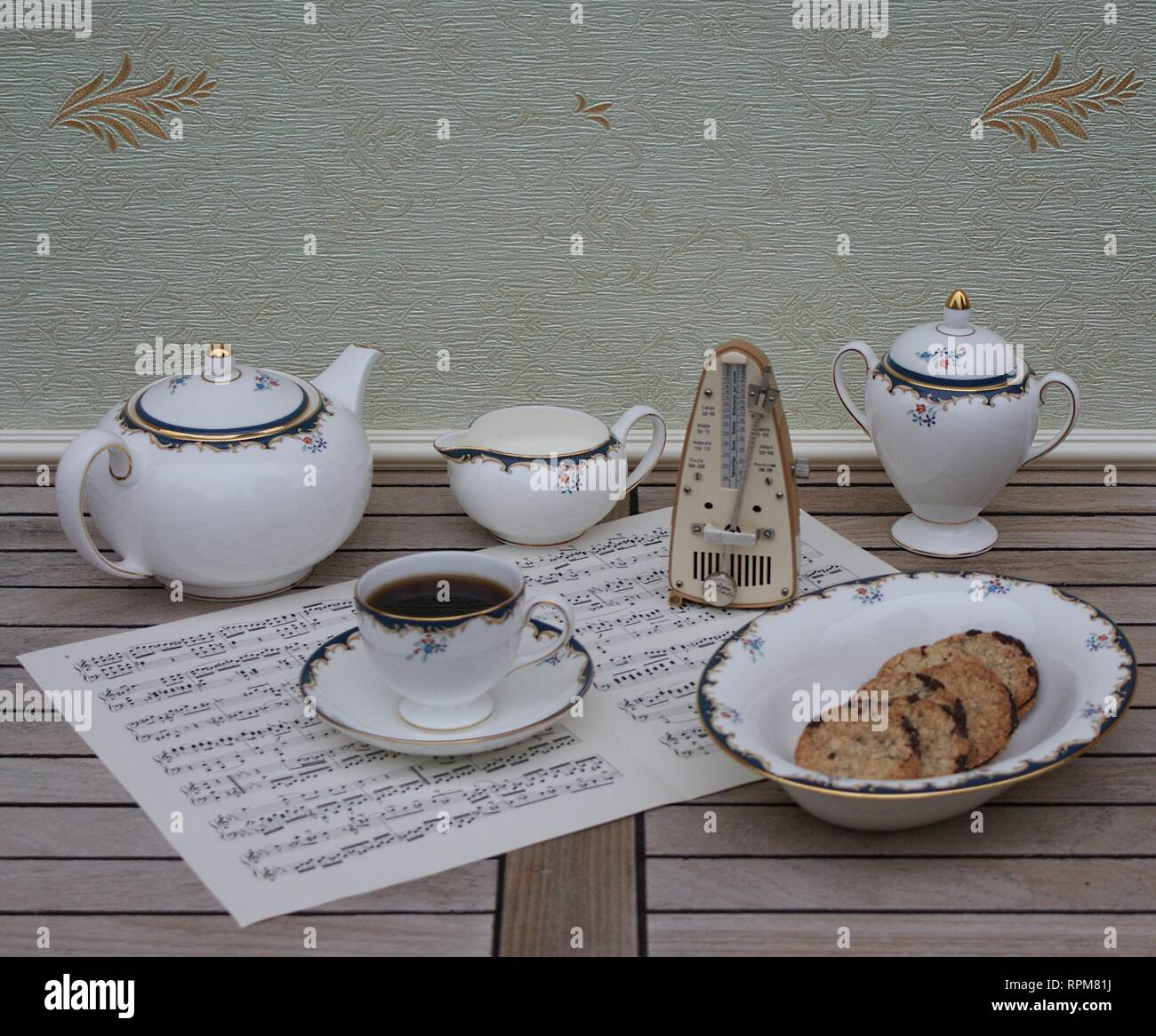 English teacup with saucer, teapot, cream jug, sugar bowl and a cake bowl, fine bone china porcelain, and a metronome for music on a sheet of music - Stock Image