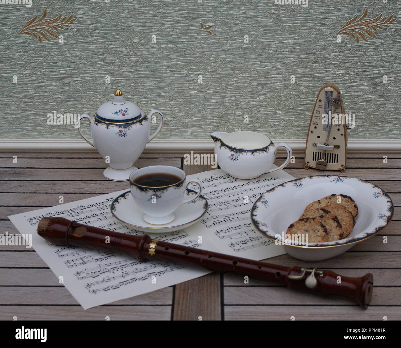 English teacup with saucer, cream jug, sugar bowl and a cake bowl, fine bone china porcelain metronome for music and a block flute on a sheet of music - Stock Image