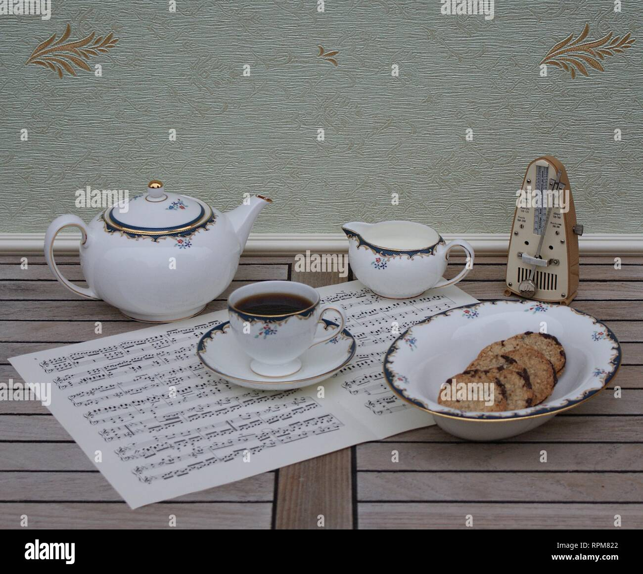 English teacup with saucer, teapot, cream jug and a cake bowl, fine bone china porcelain, and a metronome for music on a sheet of music - Stock Image
