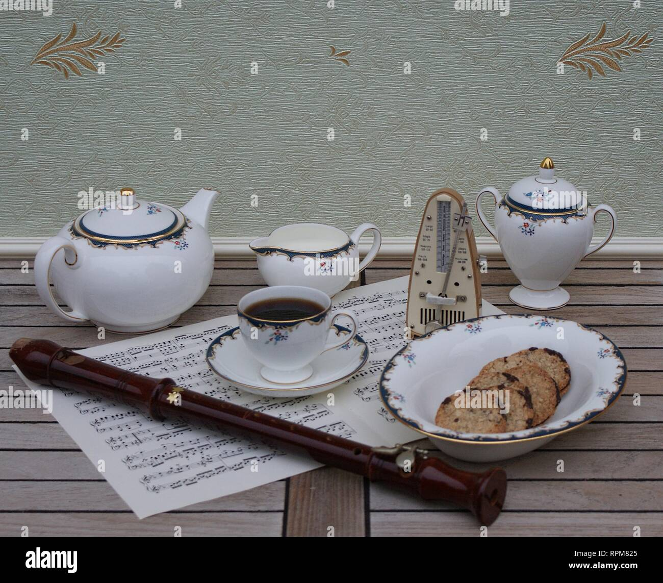 English teacup with saucer, teapot, cream jug, sugar bowl and a cake bowl, metronome for music and a block flute on a sheet of music - Stock Image