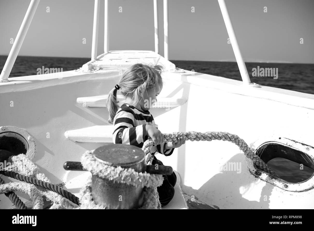 Boy in sailor shirt sail in blue sea. Child pull rope on yacht on sunny day. Travel destination cruise, travelling. Adventure, discovery, wanderlust. Summer vacation concept. - Stock Image
