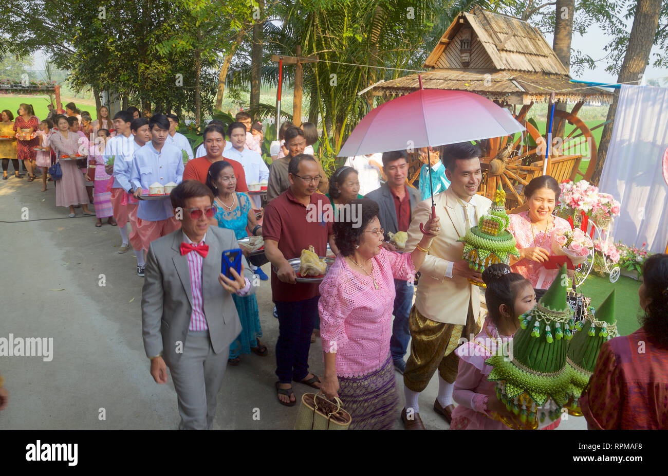 A Thai wedding party with the groom at the front waiting to be aloud in to see his bride. Thailand - Stock Image