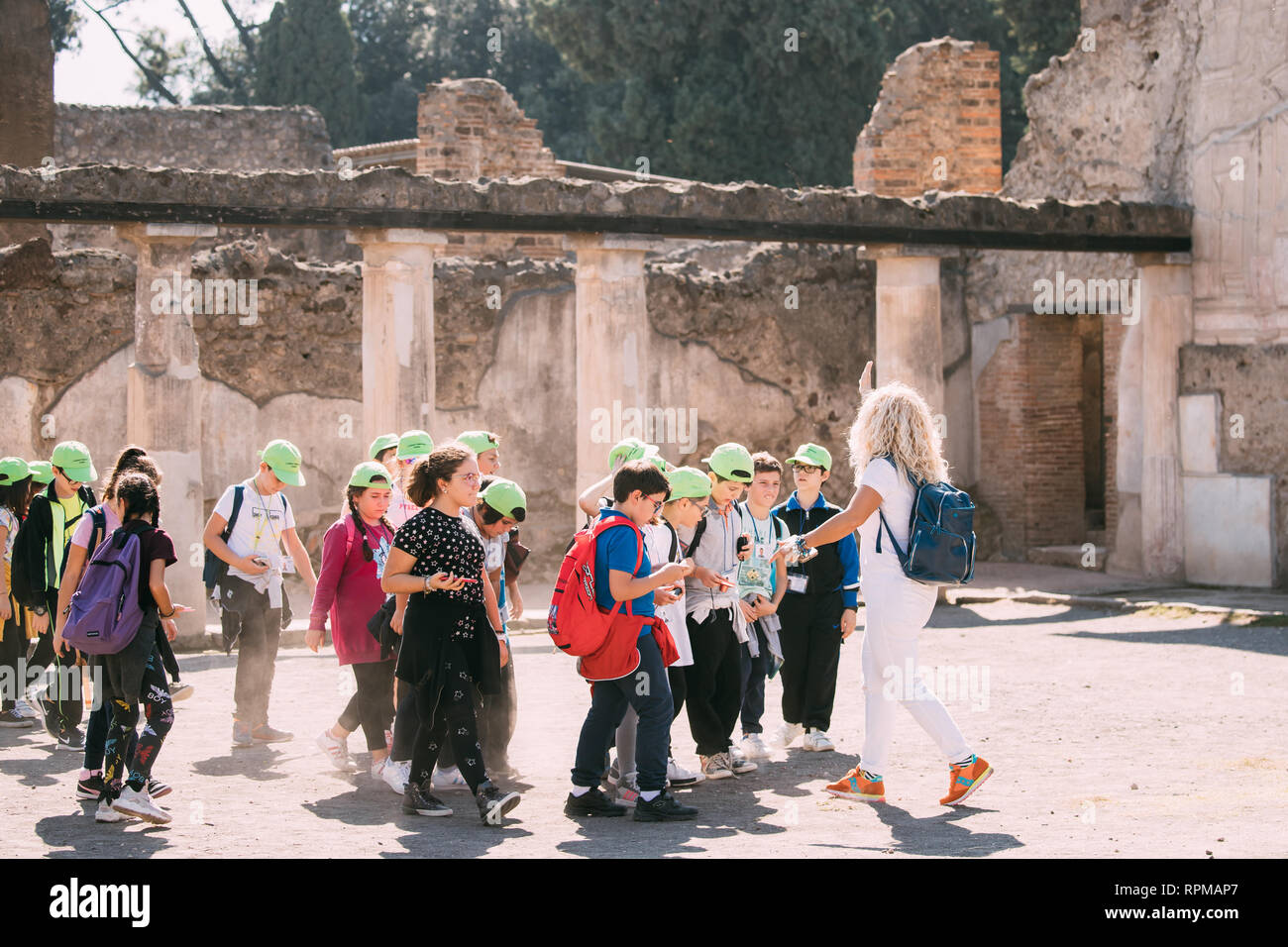Pompeii, Italy - October 18, 2018: Group Of Schoolchildren Walking On Excursions Near Remains Of Ancient Building In Sunny Day - Stock Image