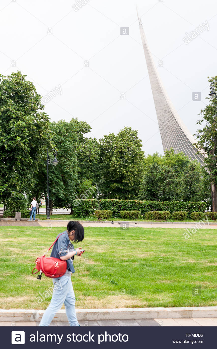 Woman passing by with Conquering the cosmos monument in behind (Moscow) - Stock Image