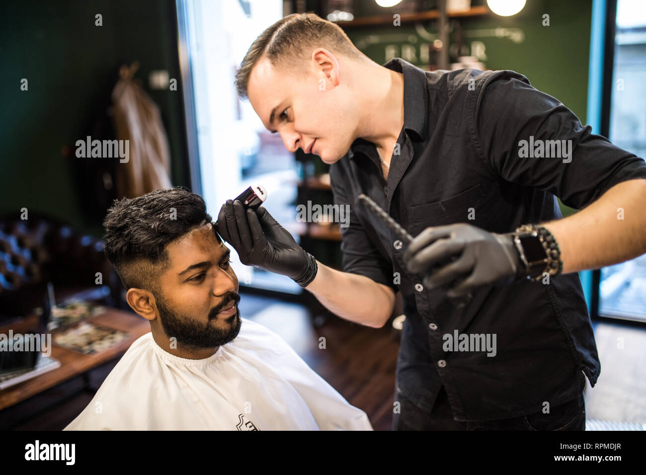 Professional hairdresser doing haircut men\u0027s hair. Cutting