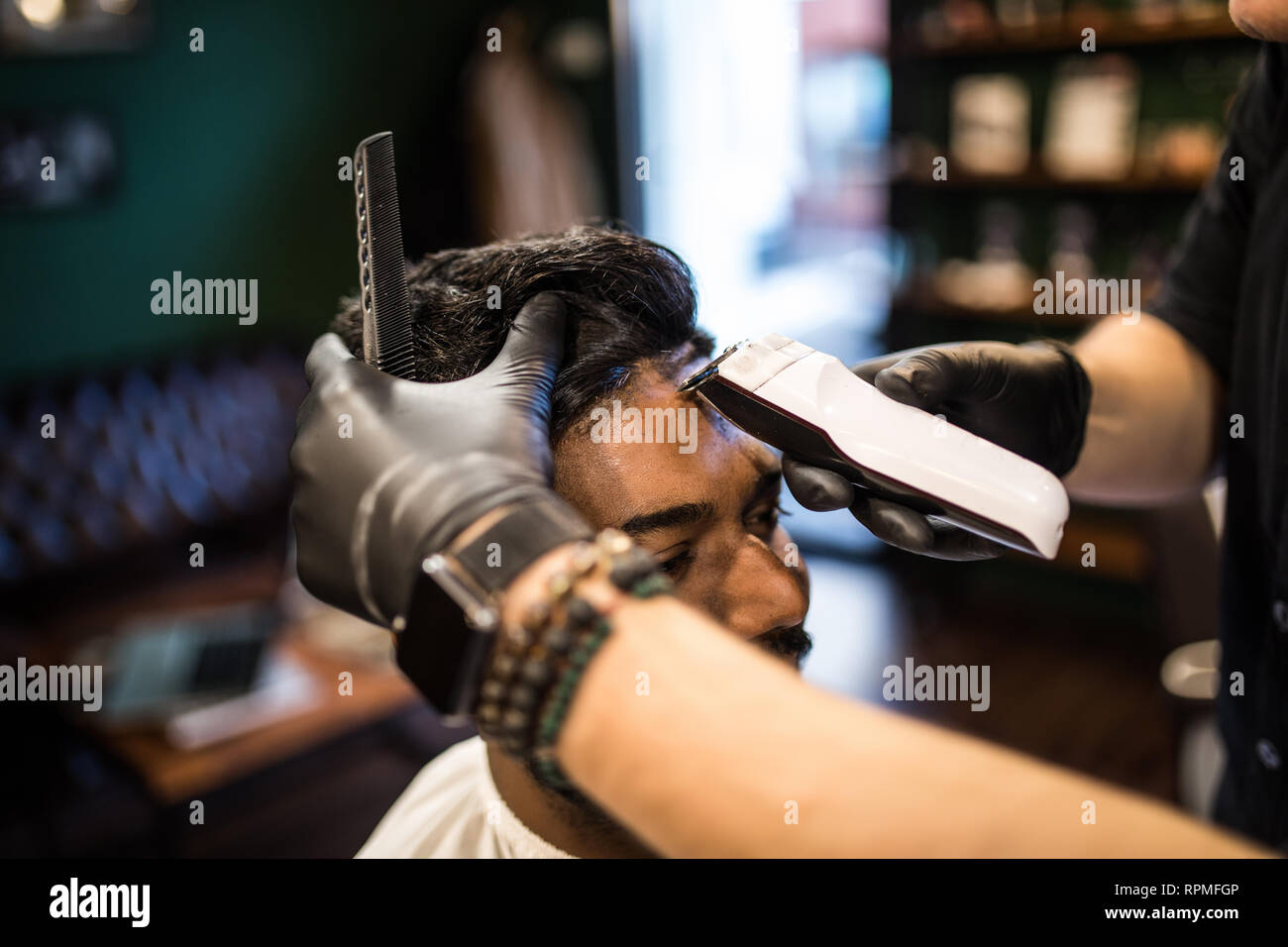 Professional hairdresser doing haircut men's hair. Cutting electric razor. Beauty saloon. Male beauty. The client is a hipster. - Stock Image