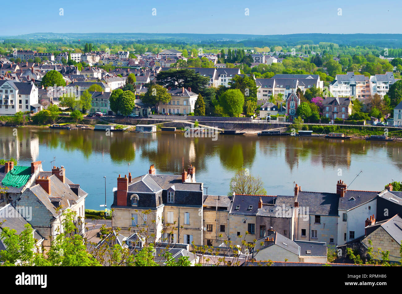 Breathtaking view on amazing small town Saumur, France. Many white and gray houses near a Loire river, lots of green trees and rooftops. Warm spring m Stock Photo