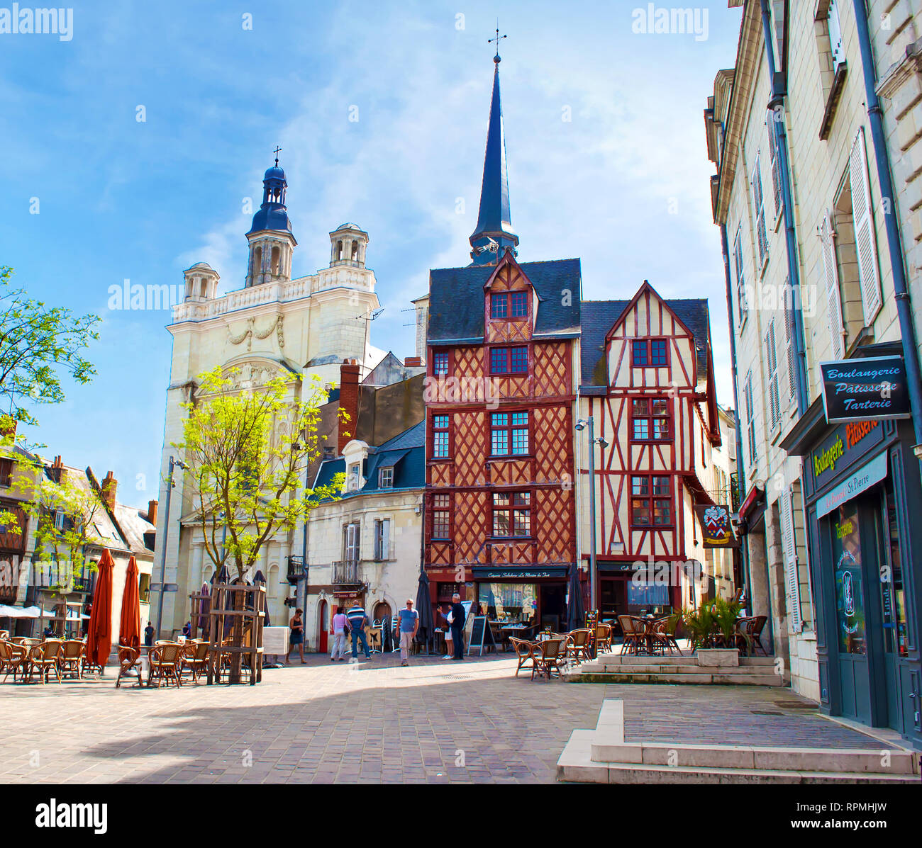 Saumur, France - April 22, 2018: Eglise St Pierre square in solitary city center of a small town Saumur, orange beam houses near a square on a warm sp - Stock Image