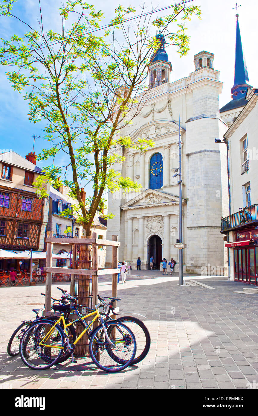 Saumur, France - April 22, 2018: Eglise St Pierre church in solitary city center of a small town Saumur, orange beam houses, parked bicycles, warm spr - Stock Image