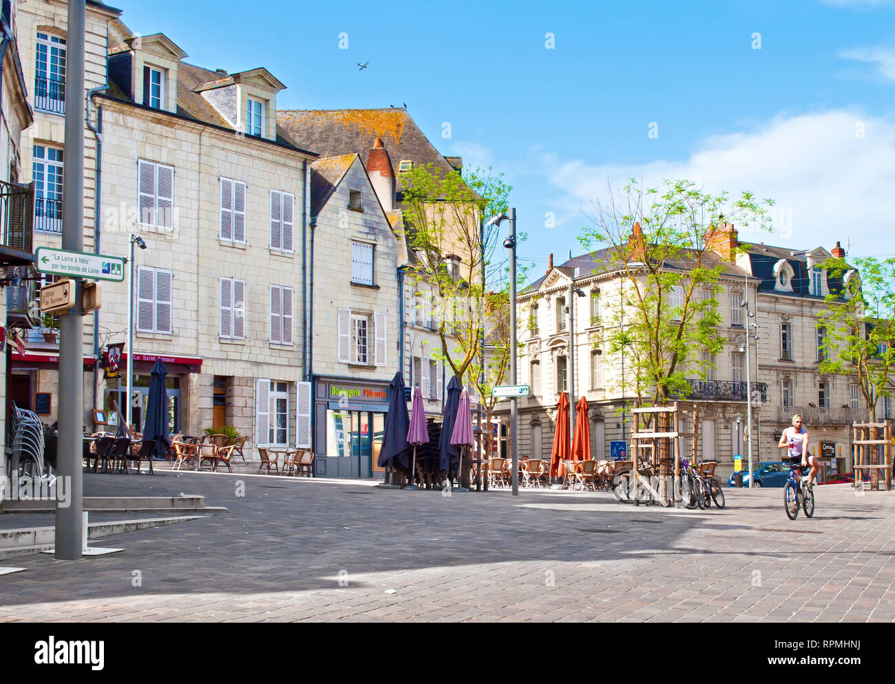 Saumur, France - April 22, 2018: One man on a bicycle at Eglise St Pierre square in solitary city center of a small town Saumur on a warm spring morni - Stock Image