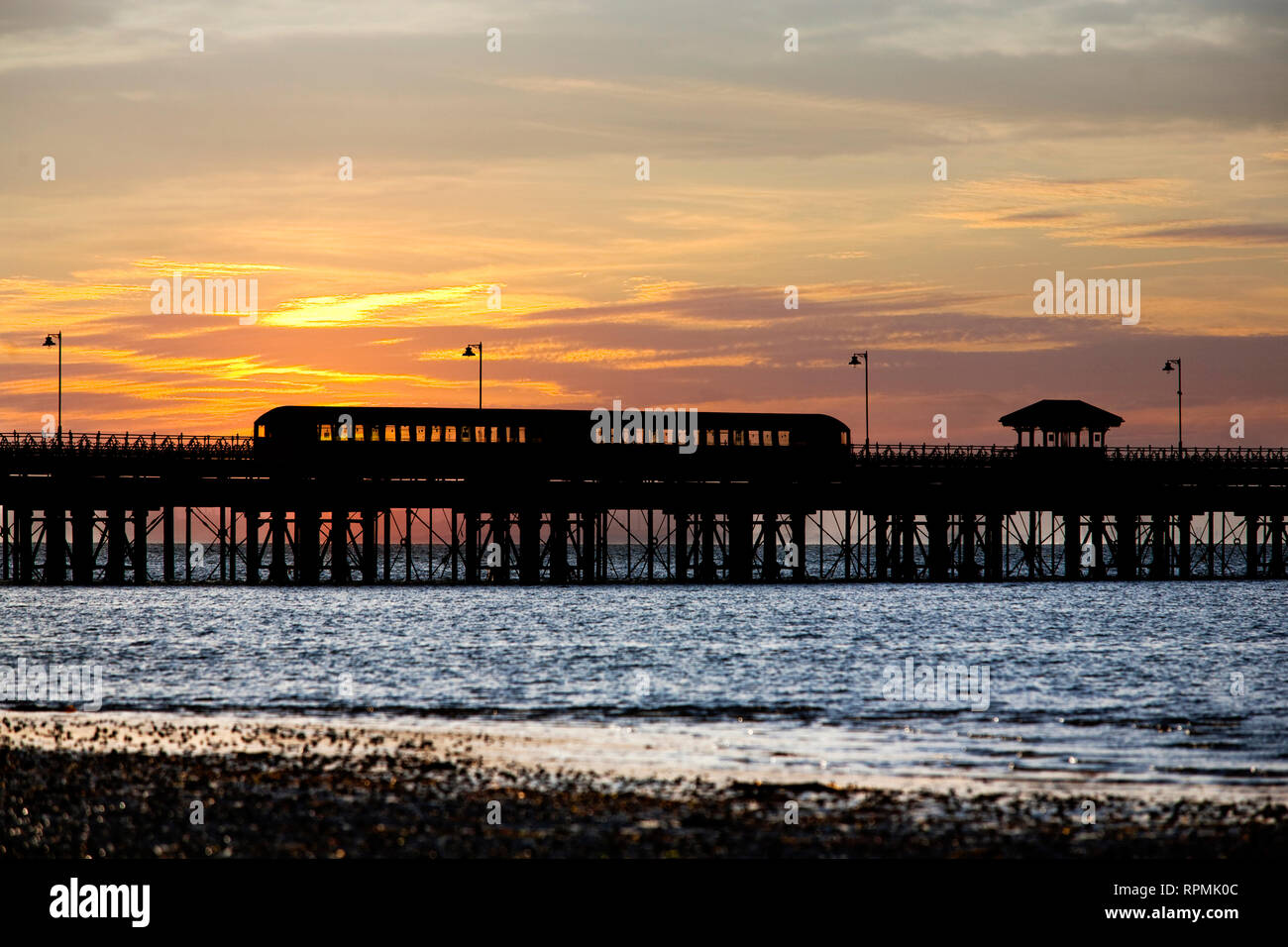 1930s tube train on Ryde Pier in silhouette against sunset, Island Line, railway, Sandown, Shanklin, UK, England, Isle of Wight, Ryde - Stock Image