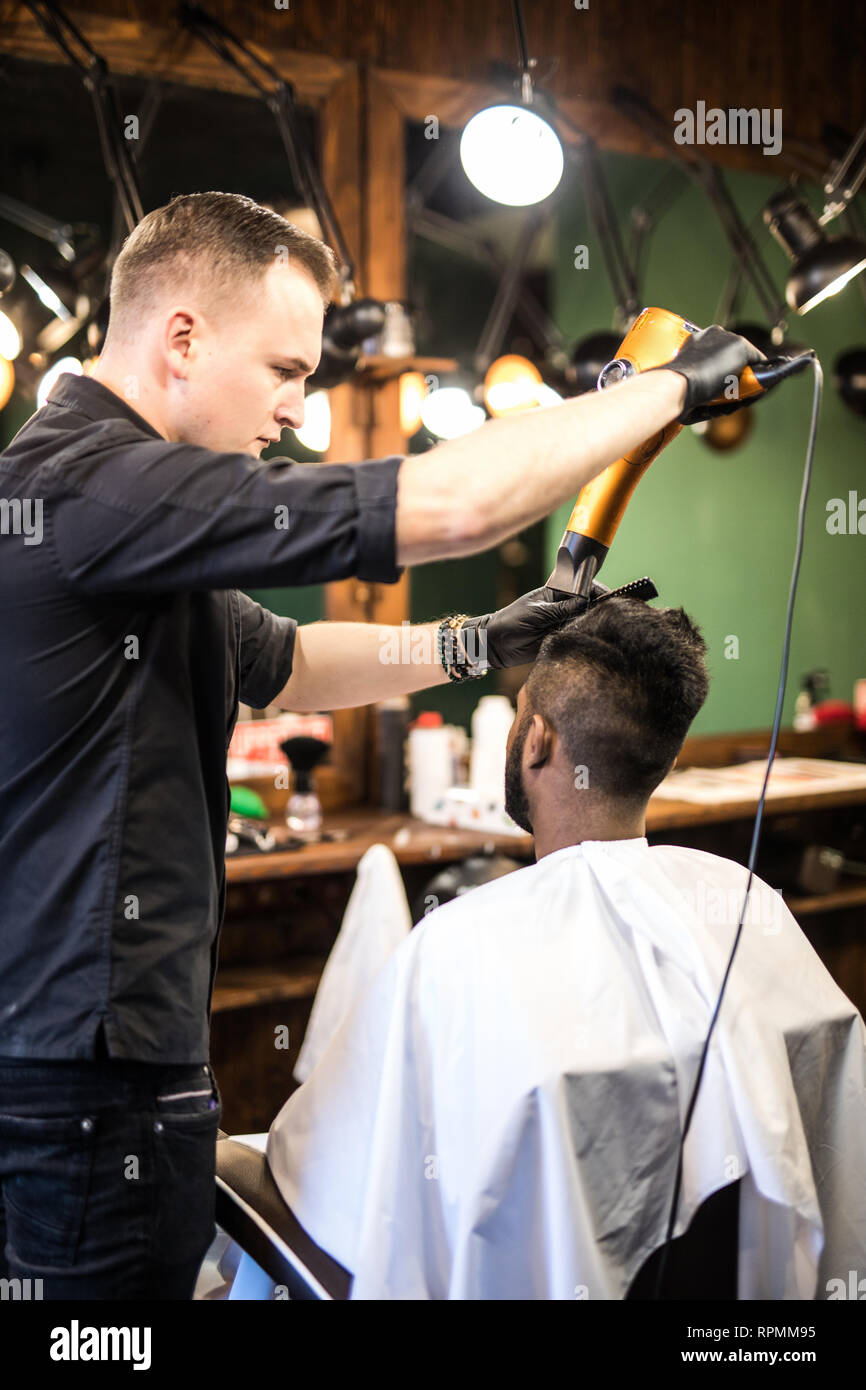 395d0c1e43b Barber with hairdryer drying and styling hair of client. Barber with  hairdryer works on hairstyle for bearded man, barbershop background. Hipster  bear