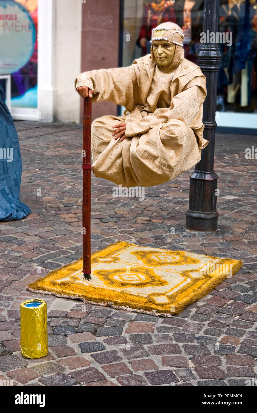 male mime, suspended above sidewalk; rug, gold face, clever; earning money; job, imaginative, shopping street; Trier; Germany; vertical - Stock Image