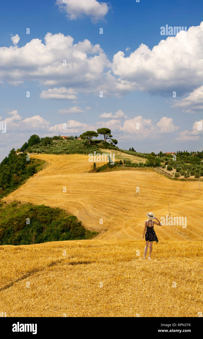 A young woman with a short dress and a straw hat admiring the rolling hills in front of her from a cut hay field in Val d'Orcia, Tuscany, Italy Stock Photo