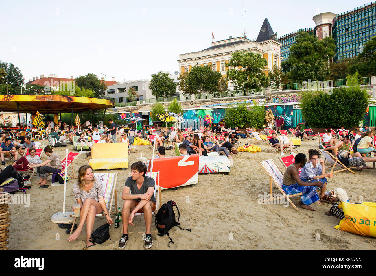 People chilling at Strandbar Herrmann, Vienna's urban beach, open from mid-April to early October, along the Danube canal (Donaukanal) - Stock Image