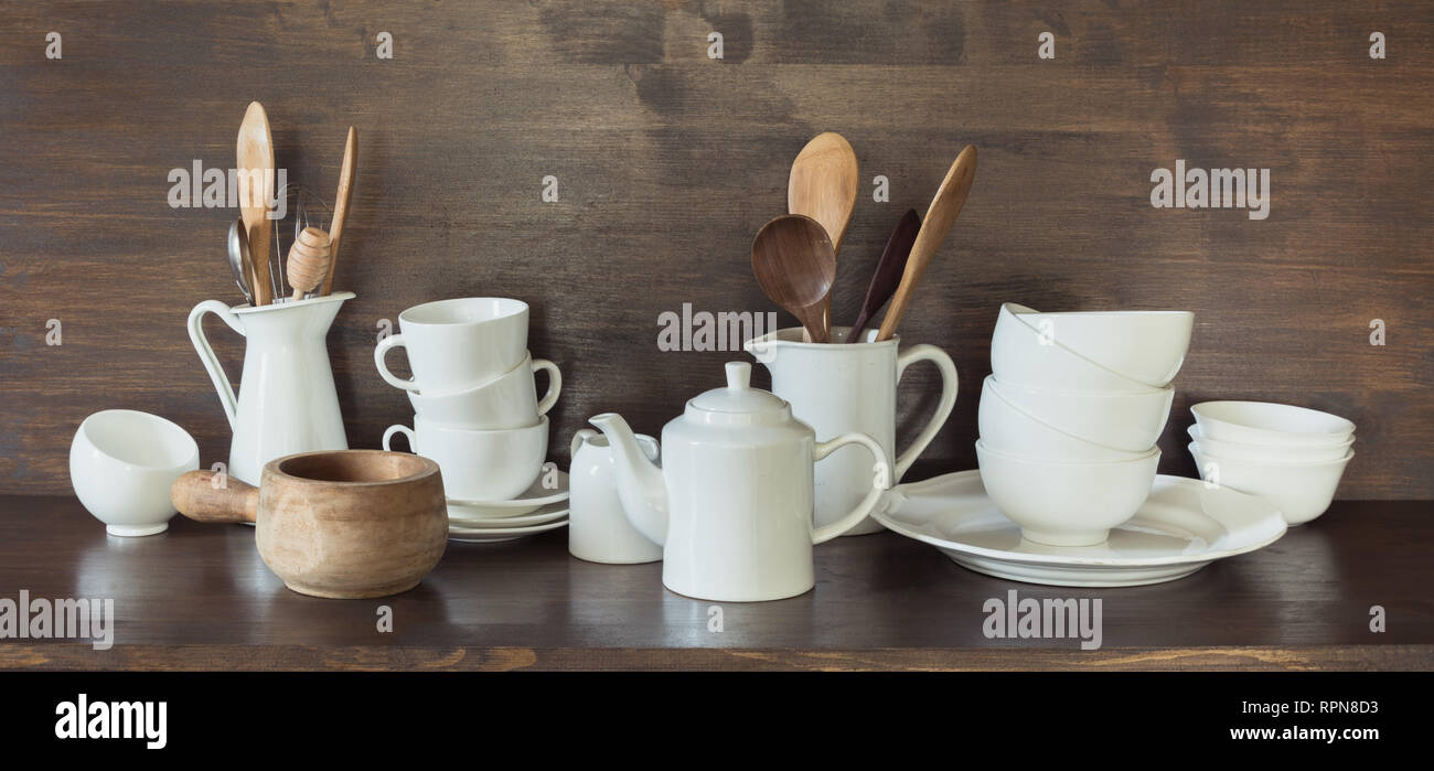 Crockery, porcelain, white utensils and other different stuff on wooden countertop. Kitchen still life as background for design. Stock Photo