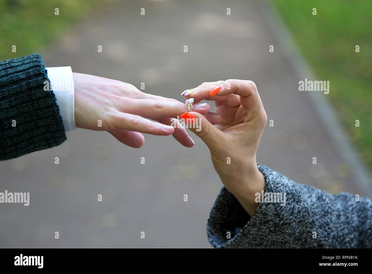 Close-up Of Woman's Hand Putting Golden Ring On Man's Finger - Stock Image
