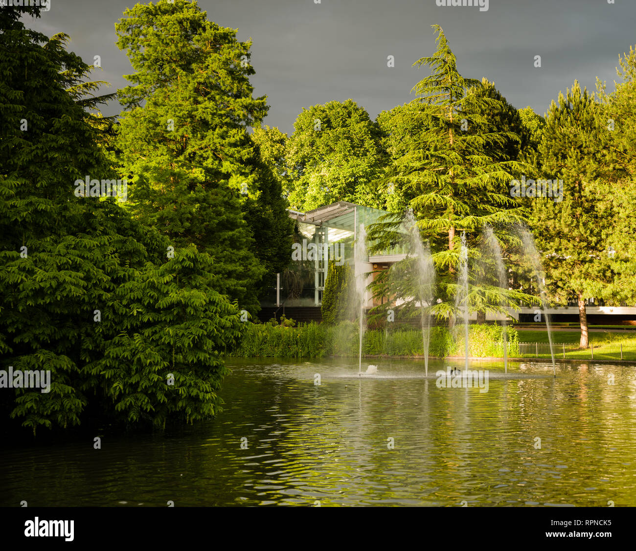 Jephson Gardens lake with fountain and the Tropical House in bright sunlight with a dark sky. - Stock Image