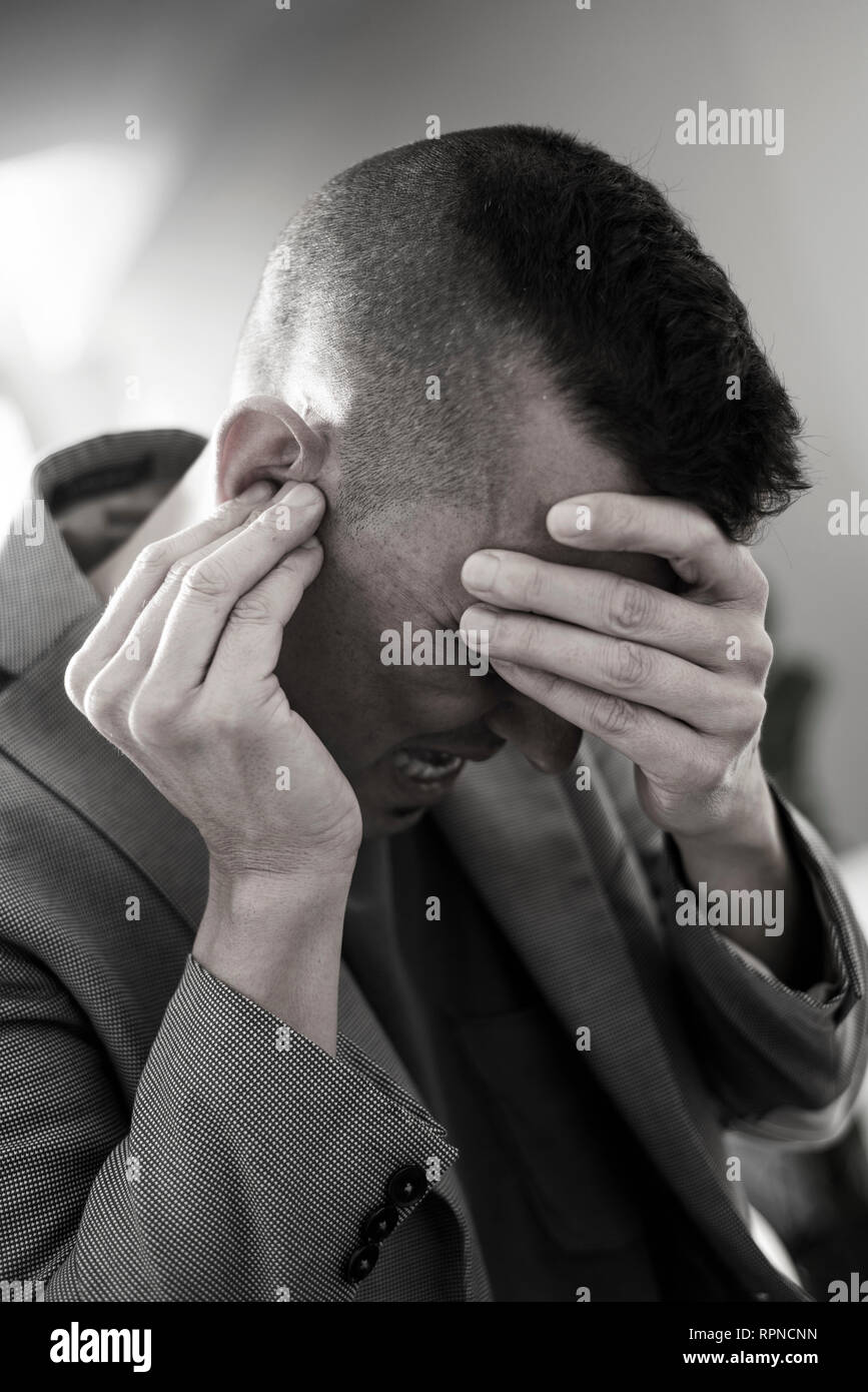 closeup of a suffering caucasian man with one hand in his head and the other hand covering his ear - Stock Image