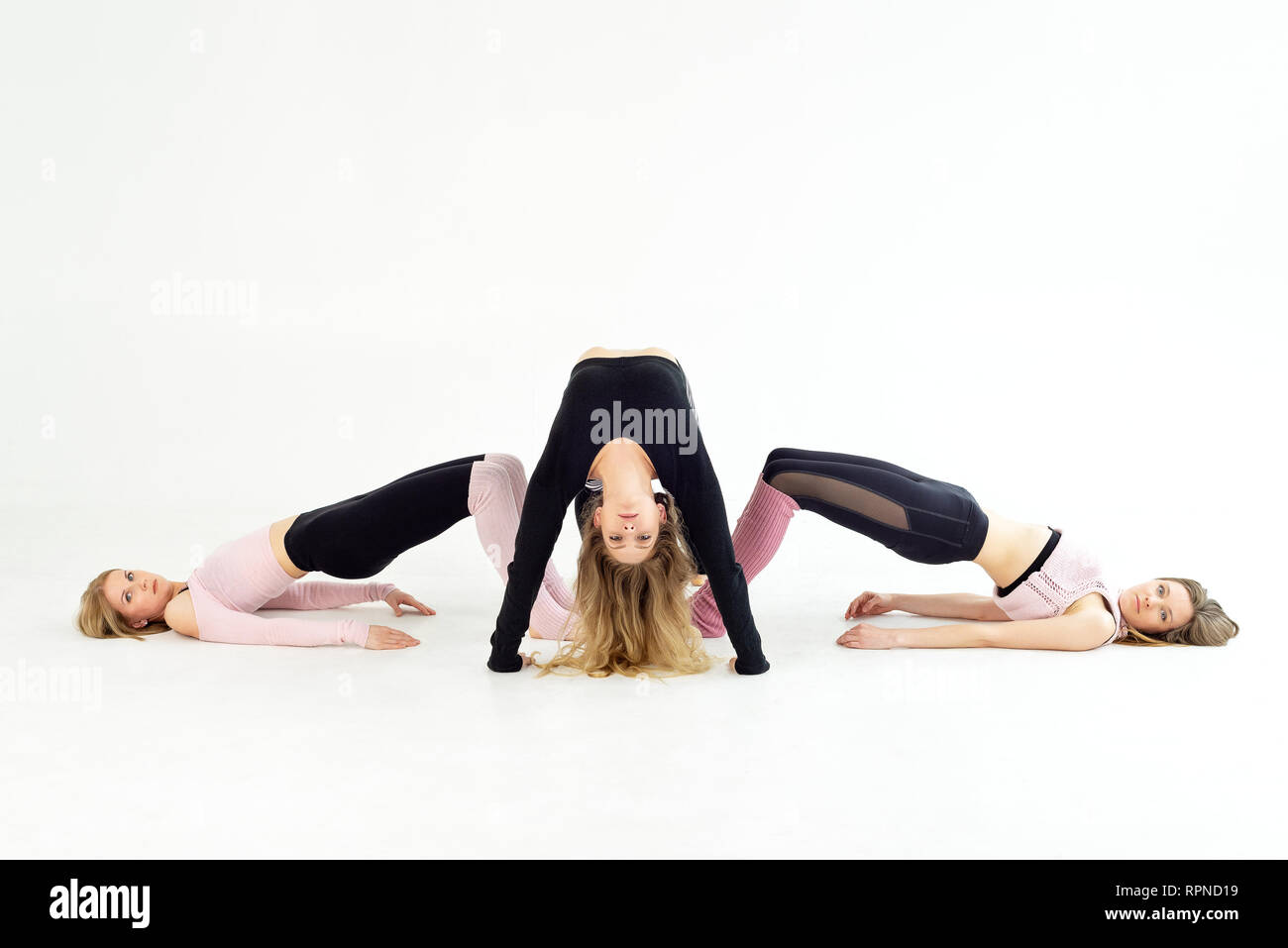 young sport girl practicing yoga, pilates bend over backwards. white background - Stock Image